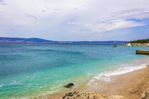 areia maravilhosa e praia rochosa e promenade novi vinodolski croatia. foto