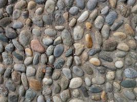 uma parede construída com uma mistura de pedras redondas e cimento foto