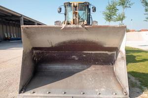 balde de trator de ferro. veículo da fábrica produzindo concreto foto