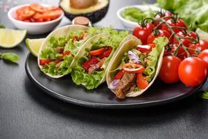tacos mexicanos com carne, tomate, abacate, cebola e molho de salsa foto