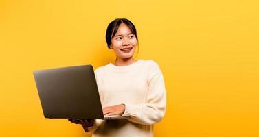 conceito de comunicação online menina asiática usar laptop em casa amarelo foto