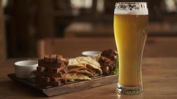 variedade de lanches de cerveja fresca e copo de cerveja. prato de cerveja no café foto