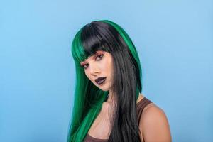 Mulher bonita usando meia peruca preta colorida verde contra o azul foto