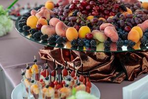 mesa com uma variedade de petiscos de frutas e frutas vermelhas. bufê para companhia foto