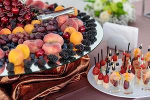 mesa com uma variedade de petiscos de frutas e frutas vermelhas. bufê foto