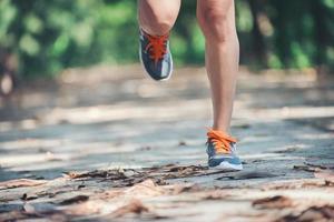 pernas de uma mulher saudável durante a corrida pela manhã no parque. foto