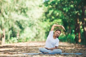 jovem mulher asiática fazendo ioga de manhã no parque. foto