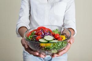 mãos de mulher bonita segurando uma tigela grande de salada vegetariana fresca. foto