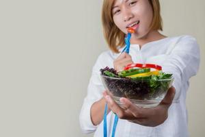 linda mulher comendo salada com fita métrica do garfo embrulhada. foto
