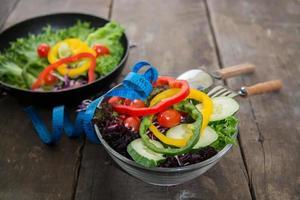 salada de legumes frescos na tigela com medição de fundo de madeira. foto