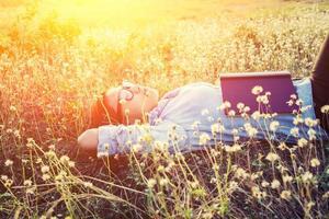 mulher jovem hippie deitada em um campo de flores depois de se cansar de ler foto
