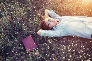 Linda jovem hippie deitada no smiley de campo de prados foto