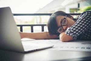 cansada mulher de negócios dormindo em um laptop enquanto trabalhava no local de trabalho foto