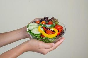linda mulher segurando uma tigela de salada vegetariana fresca foto