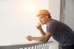 jovem hippie descansando na varanda de casa com o nascer do sol foto
