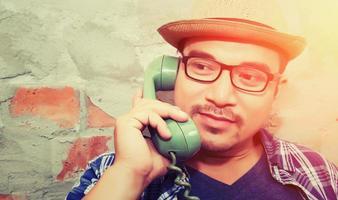 homem bonito hippie falando com telefone retro no fundo de tijolos foto