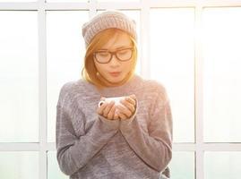 mulher hipster segurando uma xícara de café perto da janela parece tão linda foto