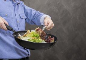 jovem cozinhar alimentos saudáveis na cozinha. foto
