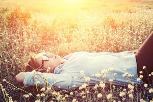 mulher deitada no campo dente-de-leão fecha os olhos e se sente confortável foto