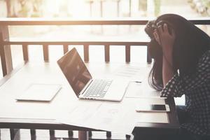 mulher com as mãos na cabeça enquanto está sentada em seu local de trabalho no escritório. foto