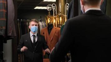 homem verificando o ajuste de seu terno com uma máscara foto