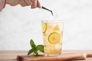 estilista alimentar usa pinças para decorar chá gelado com limão foto