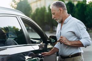 homem de negócios sênior entra em seu carro após um dia de trabalho árduo foto