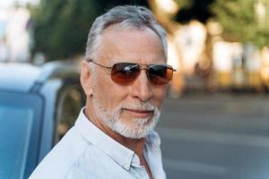 retrato de homem sênior ao ar livre em uma camisa e óculos escuros foto
