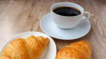 xícara de café quente e croissant lanche da manhã foto