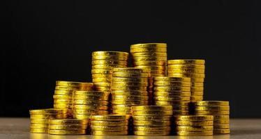 empilhar moedas de ouro em fundo preto e conceito de economia futura foto