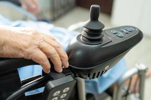 paciente idosa asiática em cadeira de rodas elétrica em hospital de enfermagem foto