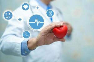 médico segurando coração vermelho no hospital, conceito médico. foto