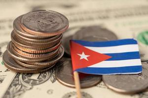 pilha de moedas com a bandeira de cuba em fundo de notas de dólar dos EUA. foto