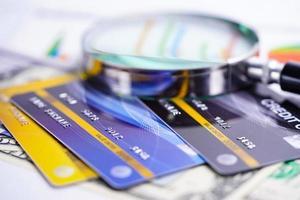 lupa com cartão de crédito em papel de gráficos foto