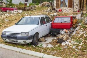carros velhos quebrados estacionados em um jardim caótico em novi vinodolski, croácia foto