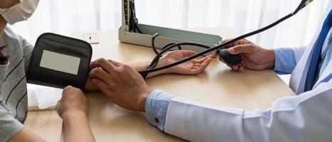 médico usando esfigmomanômetro para medir a pressão arterial do paciente foto