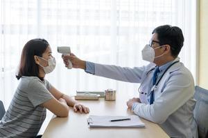 médico usando termômetro digital para medir a temperatura do paciente foto
