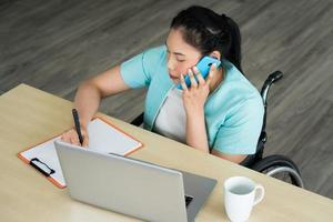 Mulher asiática com deficiência sentada em cadeiras de rodas e trabalhando no escritório foto