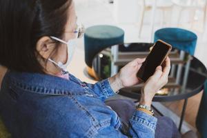 mulher usando máscara e manter o distanciamento social no café durante o surto. foto