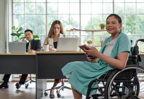jovem mulher com deficiência sentada em cadeira de rodas com colegas no escritório foto