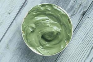 máscara de argila verde em recipiente com fundo de madeira foto