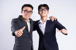 dois homens de negócios asiáticos ombro a ombro em um fundo branco foto
