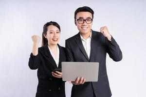 empresário asiático e mulher de negócios usando laptop em fundo branco foto