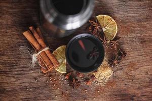Vinho quente com especiarias em uma xícara com espécies aromáticas em uma tábua de madeira rusric foto