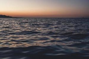 ondas do mar ao pôr do sol foto