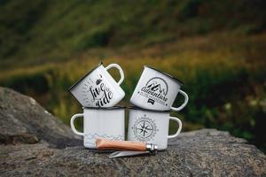 copos de metal com uma faca de turista na rocha na natureza foto