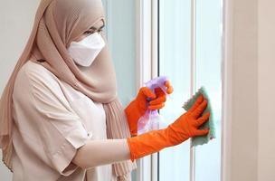 Mulher muçulmana limpando o vidro da porta com tecido e spray de álcool foto
