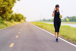 garota de esportes, mulher correndo na estrada, treinamento de mulher saudável foto