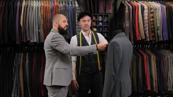 câmera lenta de homem bonito, escolhendo um design de terno com alfaiate no atelier. designer apresentando o traje no menequin ao comprador foto