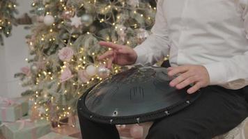 um homem joga pendurar na sala com decoração de natal. músico toca o tambor do tanque. músico toca o handpan. músico toca tambor de língua de aço foto